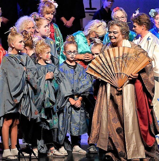 Cobien als Katisha met waaier en schoolkinderen tijdens opera