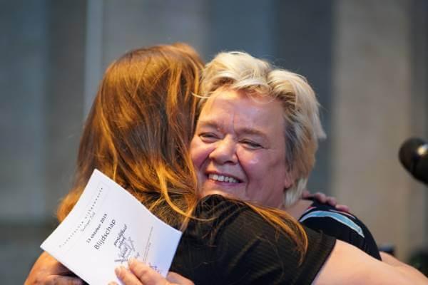 Cobien omarmd door dochter Emma tijdens Koninklijke onderscheiding