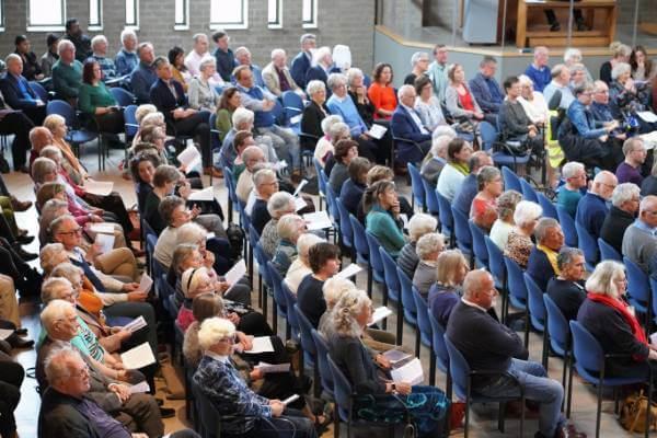 Publiek in kerk bij Koninklijke onderscheiding van Cobien